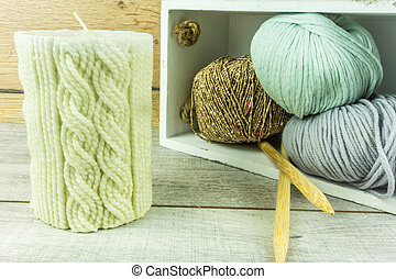 Colored wool ball with needles and a candle with knitted pattern