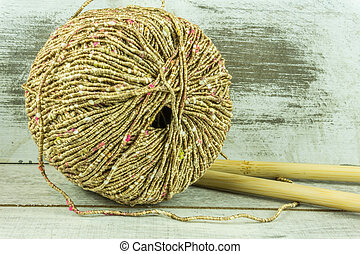 Colored wool ball with needles on a rustic wooden table