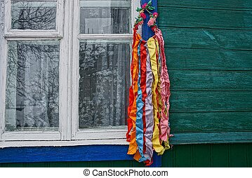 colored wreath with ribbons hanging on the wall of a house by the window in the street