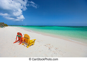 Colorful adirondack lounge chairs at Caribbean beach -...