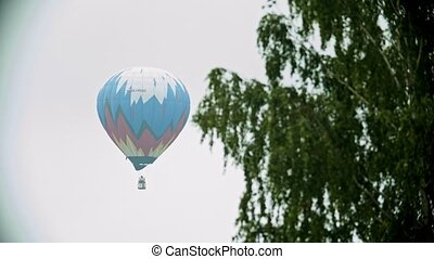 Colorful air balloon flying on a background of white sky....