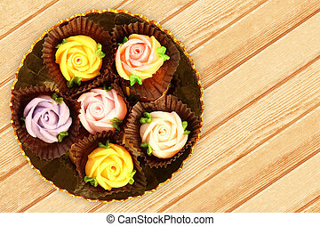 colorful allauch candy roses on wood background