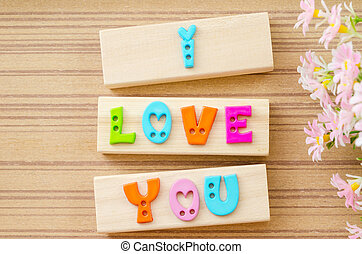 Colorful alphabet of LOVE wording on wooden background.