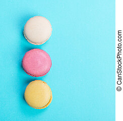 Colorful and tasty French Macarons on blue background. Top view.