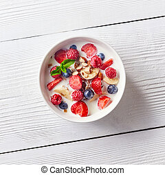 Colorful and tasty ready breakfast from corn muesli, berries, milk, almonds, slices banana on a bowl on a white wooden table with copy space. Flat lay.