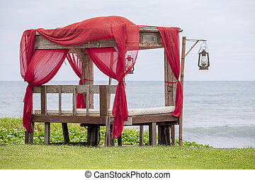Colorful arch gazebo pavilion made of wood and red textile at tropical beach in Bali, Indonesia