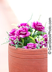 Colorful artificial flowers in clay pot.