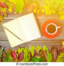 Colorful autumn background with autumnal leaves book and coffee cup