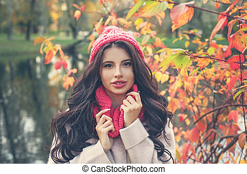Colorful autumn portrait of beautiful woman in pink hat and scarf outdoors