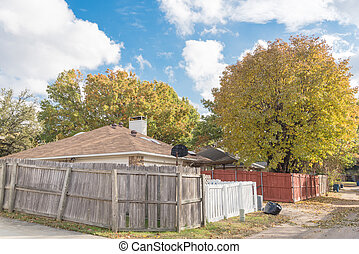 Colorful backyard of typical residential house with wooden fence and fall foliage