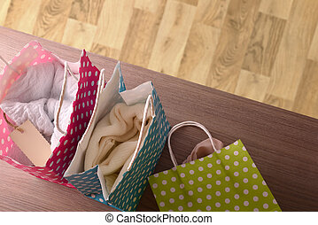 Colorful bags with clothes on wood table and parquet background