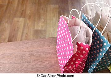 Colorful bags with clothes on wood table parquet background elevated