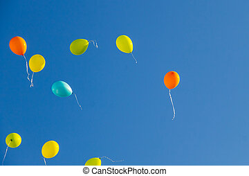 Colorful balloons flying in blue sky