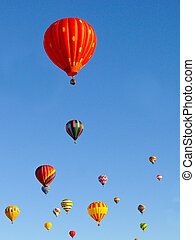 Colorful balloons rising in a blue sky