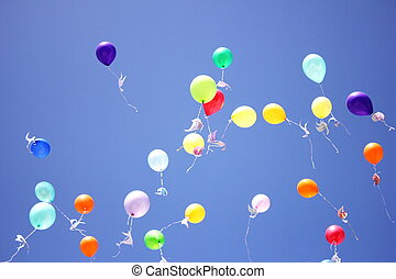 Colorful balloons with paper pigeons tied to them fly in the blue sky