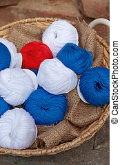Colorful balls of wool and cotton yarn in a basket on the rustic background