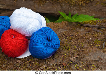 Colorful balls of wool and cotton yarn on the rustic background