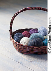 Colorful balls of wool yarn in a basket on the rustic background