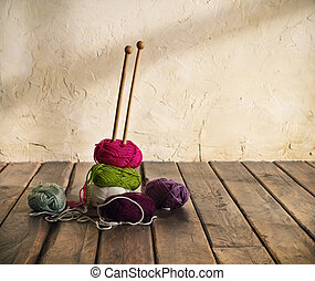 Colorful balls of yarn on a wooden table. Retro style