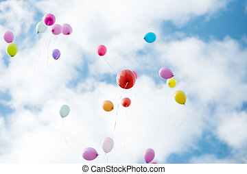 Colorful baloons flying in blue cloudy sky.