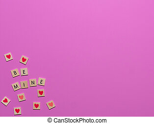 Colorful Be Mine valentine game tiles with hearts in the corner of a pink background