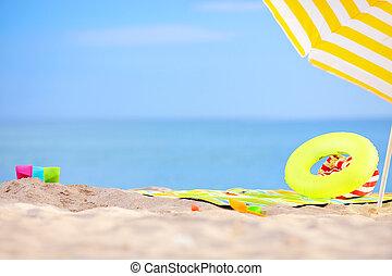 colorful beach items on sand near the sea