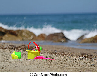 colorful beach toys, bucket and shovel, in sand with sea view