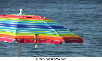 A rainbow colored umbrella stands by the ocean provoking happy thoughts of summer, holidays and vacations.