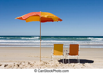 Colorful Beach Umbrella - Beach umbrella and two chairs at...