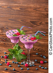 Colorful berry smoothies on a wooden background. Healthy cold milkshake with blueberries, mint, raspberries. Copy space.