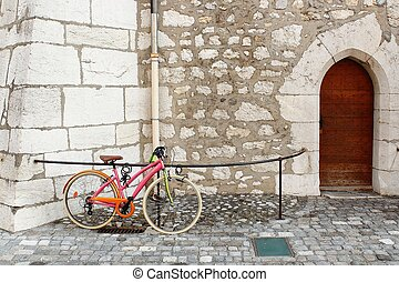 Colorful bike in the city of Annecy staying near the entrance to the Church