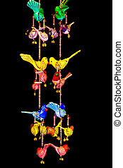 Colorful bird hangings on black background