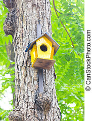 Colorful birdhouse made of wood up in a tree.