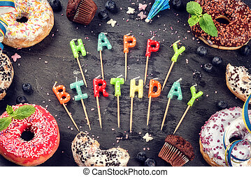 Colorful birthday background with donuts and cupcakes on dark background