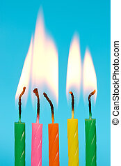 birthday candles burn on blue background