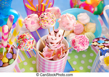 colorful birthday party table with homemade pink marshmallow pops and other sweets for kids