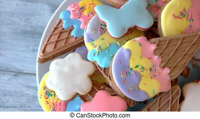 Colorful biscuits with frosting on plate.