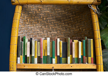 Colorful boards in form of books on bamboo shelf