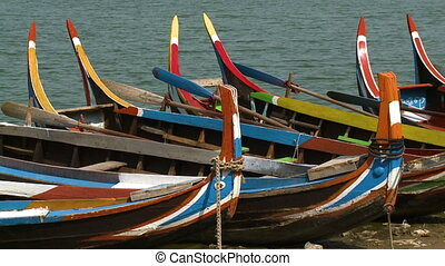 Colorful boats and paddles on the bank of a lake
