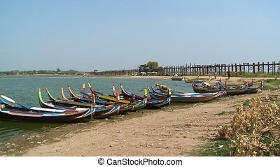 Colorful boats docked at a riverbank - A wide shot of ...