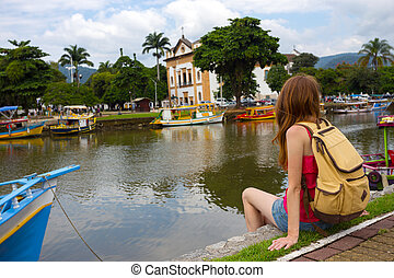 colorful boats Paraty - Tourist girl sitting on the dock...