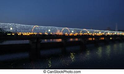 Colorful Bokeh. Blurred dark background of the bridge people at night.