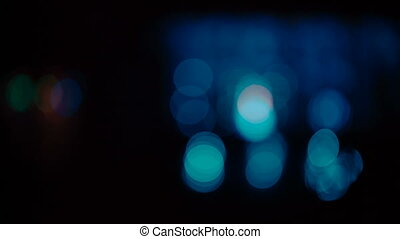 Colorful bokeh lights moving on a black background.