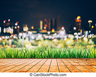 Colorful bokeh of city skyline from wood table in night time