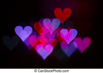 Colorful bokeh on a black background, in the form of heart