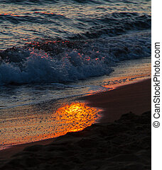 Colorful breaking waves on shore and sun reflections at sunset