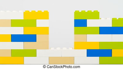 Colorful bricks making wall on white background