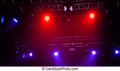 Colorful bright concert lighting equipment for stage at nightclub, illumination of entertainment musical show, party or performance - low angle. Nightlife, music, entertainment and technology concept