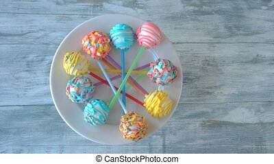 Colorful cake pops on wooden background. Plate with ball-shaped candies, top view. Desserts for childrens party.