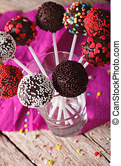 Colorful cake pops with candy sprinkles close up in a glass....